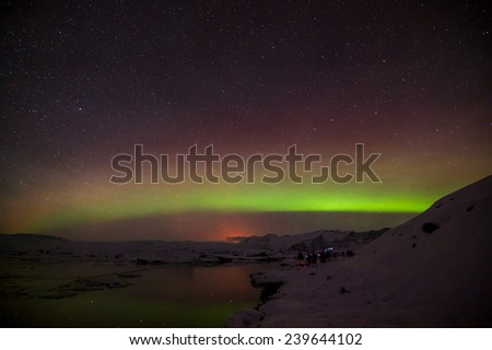A beautiful green and red aurora dancing over the Jokulsarlon lake, Iceland. - stock photo