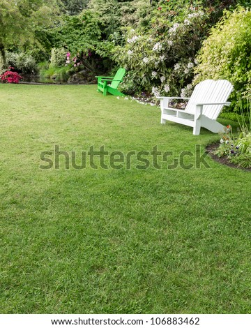 A beautiful green lawn surrounded by flowers with wooden lawn chairs - stock photo