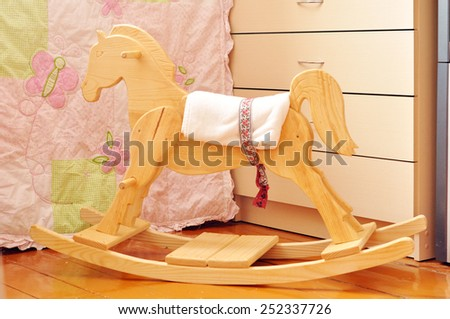 A beautiful handmade wooden horse in a kids' bedroom - stock photo