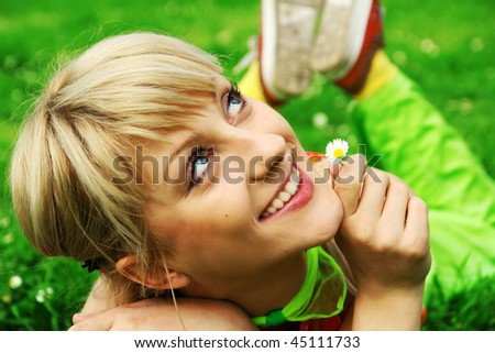 A beautiful happy blonde laying in a green meadow holding a daisy - stock photo