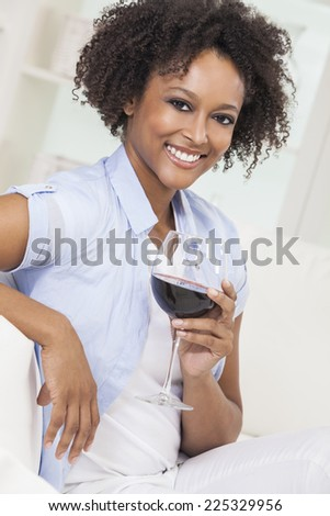 A beautiful happy mixed race African American girl or young woman drinking red wine at home on a white sofa