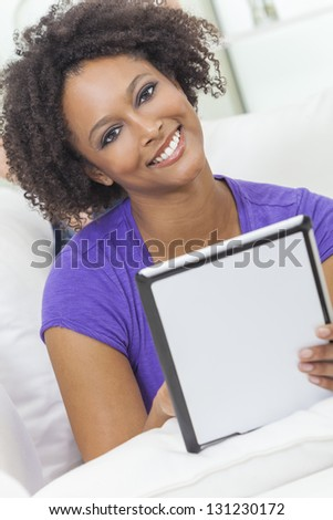 A beautiful happy mixed race African American girl or young woman laying down on sofa using a tablet computer