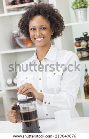A beautiful happy mixed race African American girl or young woman making coffee with a cafetiere in her kitchen at home