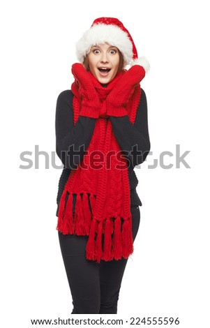 A beautiful happy surprised Christmas woman wearing santa hat and red scarf and mittens shouting of joy, over white background - stock photo