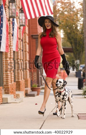 a beautiful happy woman walking her dalmatian puppy dog down the street - stock photo