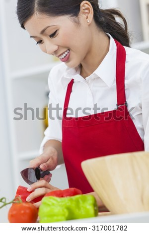 A beautiful happy young Asian Chinese woman or girl wearing a red apron cutting & preparing fresh vegetable salad food in her kitchen at home - stock photo