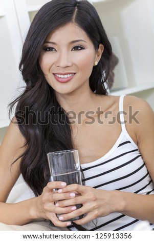 A beautiful happy young Chinese Asian Oriental woman with a wonderful toothy smile drinking a glass of water at home - stock photo