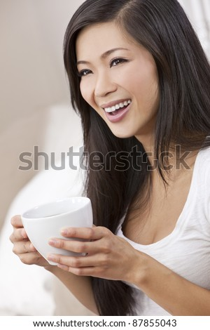 A beautiful happy young Chinese Asian Oriental woman with a wonderful toothy smile drinking tea or coffee