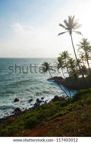 A beautiful high key tropical landscape of the ocean and rocky coastline from  a headland near the beach resort village of Mirissa, Sri Lanka - stock photo