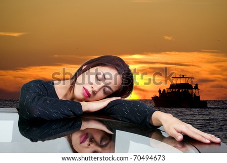 A beautiful hispanic woman dreaming about a boat sailing on the ocean at sunset.