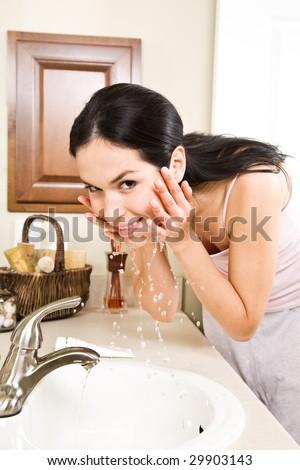 A beautiful hispanic woman washing her face in the bathroom - stock photo