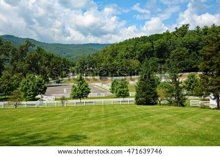 A beautiful horse farm in the mountains with white fencing