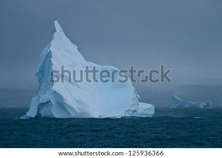 A beautiful iceberg drifts in the Southern Ocean close to Antarctica.  The colors within icebergs come from compressed gases and microorganisms. - stock photo