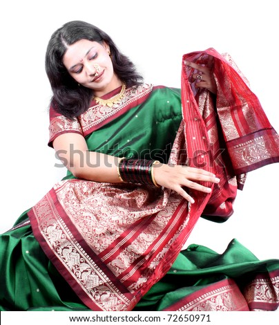 A beautiful Indian woman checking the design of her new saree. - stock photo