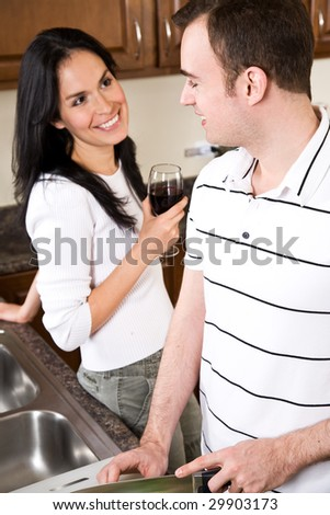 A beautiful interracial couple preparing food and having a conversation in the kitchen