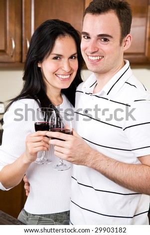 A beautiful interracial couple toasting wine in the kitchen - stock photo