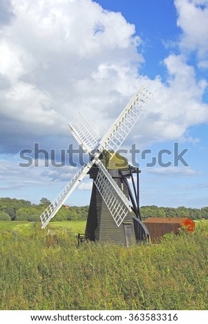 A Beautiful isolated windmill with white sails in open countryside under a stormy blue sky, Suffolk, England, United Kingdom - stock photo