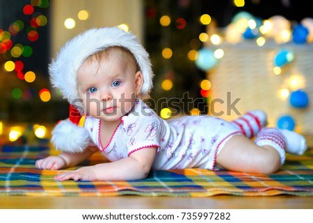 a beautiful kid in a Santa Claus hat lies on the floor against the background of bright festive garlands