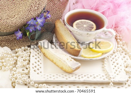 A beautiful ladies tea party with cup of tea and lemon biscotti - stock photo