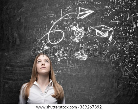 A beautiful lady is dreaming about graduation. Math formulas, an arrow, geometric figures are drawn on the black chalkboard. - stock photo