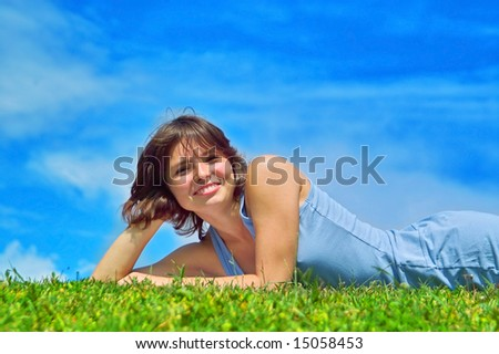 A beautiful lady lies on the grass in the sunny day