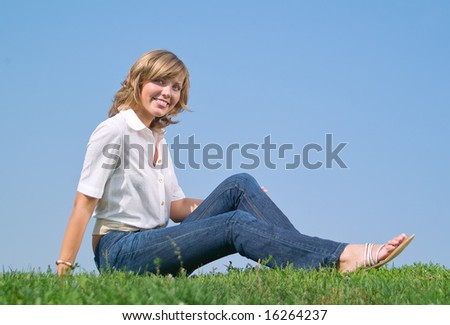 A beautiful lady sitting on the grass in sunny day