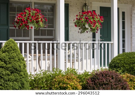 A beautiful landscaped American front porch with white railings and hanging baskets with red flowers.  - stock photo