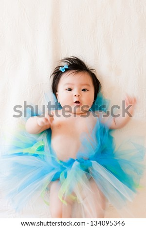 A beautiful little Asian baby girl lies back on her bed, wearing an adorable blue tutu. - stock photo