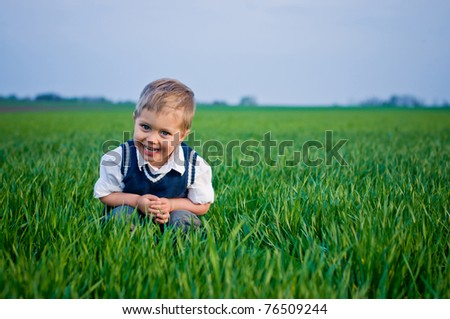 A beautiful little baby boy sitting in the grass - stock photo