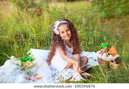 A beautiful little girl child kid laughing in white dress on grass background with basket of toys.