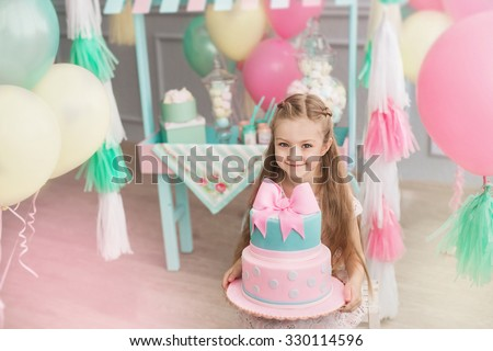 A beautiful little girl holds on a hands a big cake in a room decorated a colorful balloons and a toy candy shop - stock photo