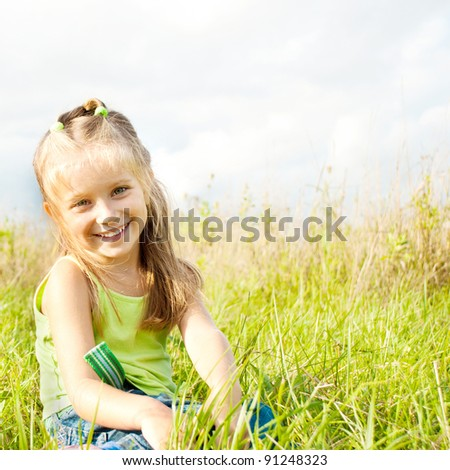 a beautiful little girl in a meadow - stock photo