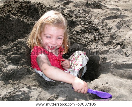 A beautiful little girl playing in the dark sand of a beach at Tennerife.