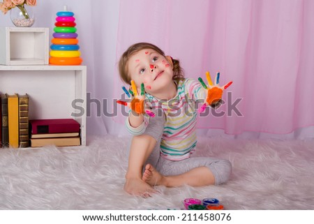 a beautiful little girl with her hands in paint, ready to prints - stock photo