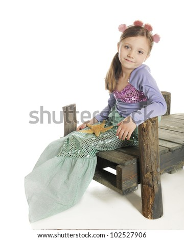 A beautiful little mermaid sitting on a rustic wood dock.  On a white background. - stock photo