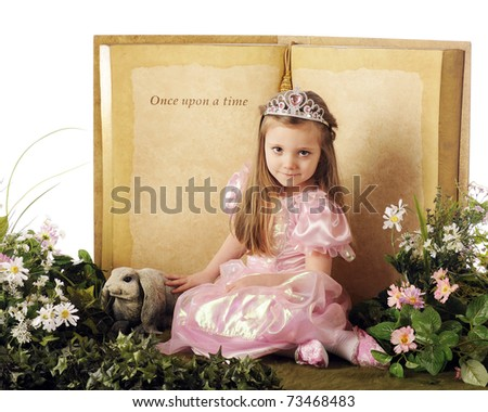 "A beautiful little princes posed before a ""Once upon a time"" book and surrounded by flowers,foliage and a bunny."