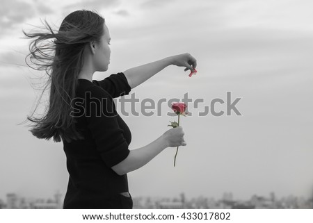 A beautiful lonely woman hoping for love in front of a city view, playing he loves me, he loves me not - stock photo
