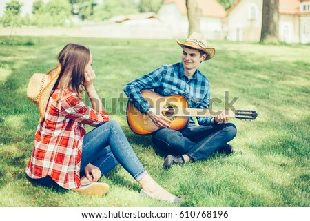 A beautiful, loving couple in cowboy style is having a good time. Guy plays the guitar outdoors in park