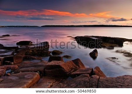 A beautiful Maine sunset with orange, pink and blue sky.  The pink granite rocks in the foreground glow from the setting sun. - stock photo