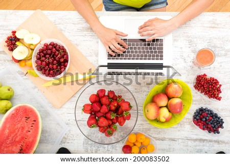 A beautiful mature woman using a Laptop computer in the kitchen with fruits. - stock photo