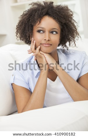 A beautiful mixed race African American girl or young woman laying down on sofa at home looking thoughtful and relaxed - stock photo