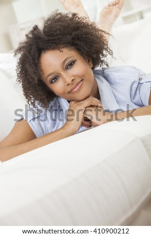 A beautiful mixed race African American girl or young woman laying down on sofa at home looking happy and relaxed