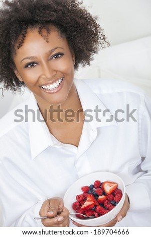 A beautiful mixed race African American girl or young woman looking happy and eating fruit salad in a bowl, raspberries, strawberries & blueberries