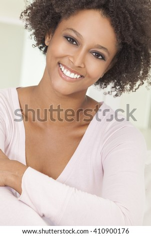 A beautiful mixed race African American girl or young woman looking happy and smiling with perfect teeth - stock photo