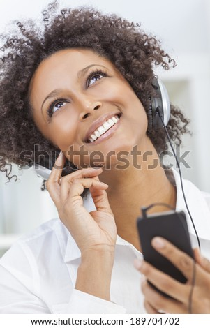 A beautiful mixed race African American girl or young woman looking up & listening to music on mp3 player and headphones - stock photo