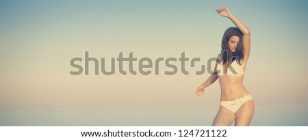 A beautiful model on the beach - stock photo