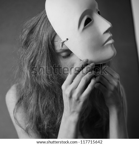 a beautiful model with white mask -  volto bianco. studio shot with daylight. - stock photo