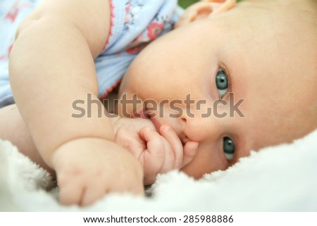 A beautiful newborn baby girl is laying down on a soft white blanket looking at the camera as she is sucking her thumb. - stock photo