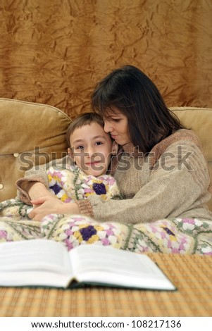 A beautiful nice mother with her son sitting on the couch on a light background