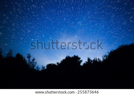 a beautiful night sky, the Milky Way, star trails and the trees - stock photo